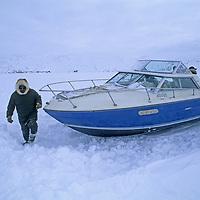 BAFFIN ISLAND, Nunavut, Canada. Inuit guide walks by stranded boat on Baffin Bay.