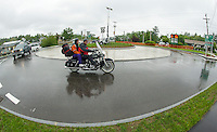 A few hardy motorcyclists arrive at Weirs Beach during the drenching rain on Friday evening for the beginning of Laconia's Motorcycle Week.   (Karen Bobotas/for the Laconia Daily Sun)