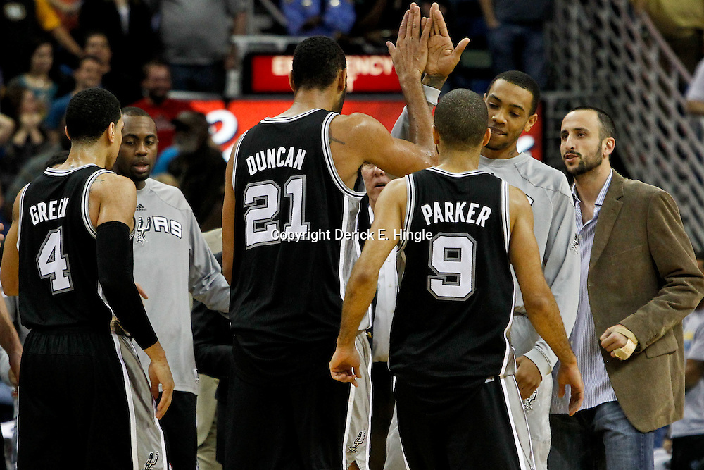 January 23, 2012; New Orleans, LA, USA; San Antonio Spurs center Tim Duncan (21) celebrates with teammates after hitting a basket with 1.4 seconds remaining in the fourth quarter of a game against the New Orleans Hornets at the New Orleans Arena. The Spurs defeated the Hornets 104-102.  Mandatory Credit: Derick E. Hingle-US PRESSWIRE
