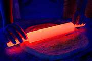 A glowing rolling pin is being used to flatten dough into the shape of a pizza.Black light