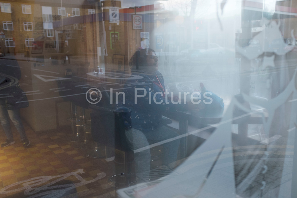 Woman lost in her own thoughts while sitting in a steamed up cafe in Whitechapel, London, UK.