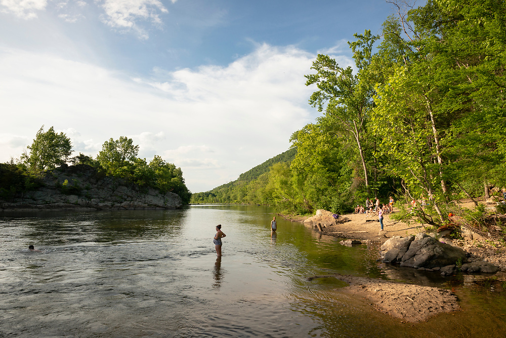 Jonesborough, Tennessee, USA - May 25, 2015: People swim and sit on the banks of the Nolichucky River beside Arnold Road near Jonesborough, celebrating the Memorial Day Holiday.
