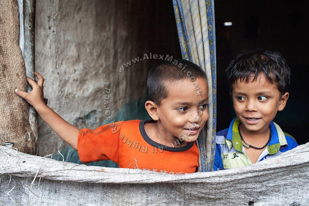 Two brothers are standing by the entrance of their home along the railway tracks passing through New Arif Nagar, one of the water-affected colonies surrounding the abandoned Union Carbide (now DOW Chemical) industrial complex in Bhopal, Madhya Pradesh, India.