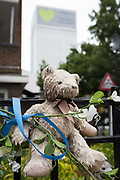 Childrens bears and cuddly toys on railings near where the Grenfell fire occured, on the first anniversary of the tower block disaster, on 14th June 2018, in London, England. 72 people died when the tower block in the borough of Kensington & Chelsea were killed in what has been called the largest fire since WW2. The 24-storey Grenfell Tower block of public housing flats in North Kensington, West London, United Kingdom. It caused 72 deaths, out of the 293 people in the building, including 2 who escaped and died in hospital. Over 70 were injured and left traumatised. A 72-second national silence was held at midday, also observed across the country, including at government buildings, Parliament.