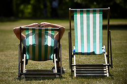 © Licensed to London News Pictures. 16/07/2019. LONDON, UK.  A man relaxes on a deckchair in the sunshine in St. James's Park.  Temperatures are forecast to rise to 26C.  Photo credit: Stephen Chung/LNP