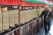 China, Tibet, Lhasa, Local Tibetans spinning prayer wheels on the Kora around the Potala Palace.