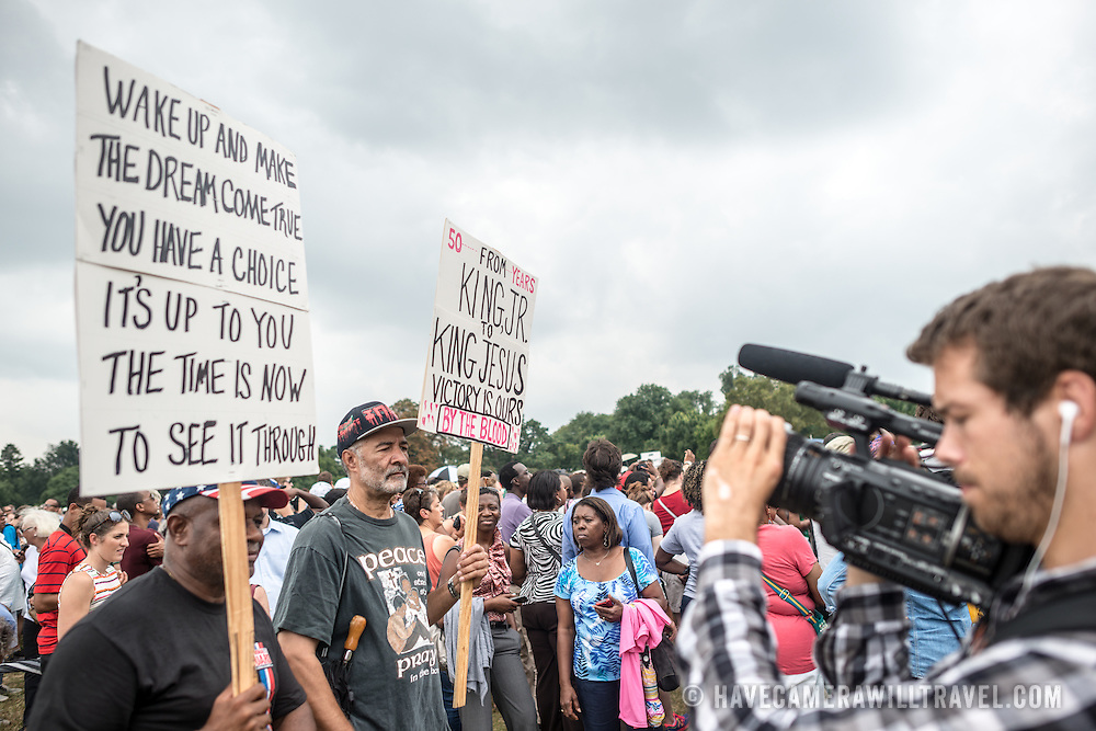 """Two men carrying placards calling on the legacy of Martin Luther King Jr's efforts on civil rights on Washington DC's National Mall at the commemoration of the 50th anniversary of the 1963 March on Washington famously remembered for civil right leader Martin Luther King Jr's """"I Have a Dream"""" speech."""