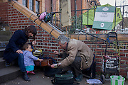 A young girl taps the guitar of a musician outside Carnegie Library in Herne Hill, south London while occupiers remain inside the premises on day 6 of its occupation, 5th April 2016. The angry local community in the south London borough have occupied their important resource for learning and social hub for the weekend. After a long campaign by locals, Lambeth have gone ahead and closed the library's doors for the last time because they say, cuts to their budget mean millions must be saved.