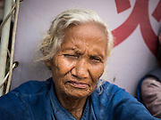 02 AUGUST 2015 - BHAKTAPUR, NEPAL:  An elderly woman in a small Internal Displaced Person (IDP) camp at Durbar Square in Bhaktapur for people left homeless by the Nepal earthquake. The Nepal Earthquake on April 25, 2015, (also known as the Gorkha earthquake) killed more than 9,000 people and injured more than 23,000. It had a magnitude of 7.8. The epicenter was east of the district of Lamjung, and its hypocenter was at a depth of approximately 15km (9.3mi). It was the worst natural disaster to strike Nepal since the 1934 Nepal–Bihar earthquake. The earthquake triggered an avalanche on Mount Everest, killing at least 19. The earthquake also set off an avalanche in the Langtang valley, where 250 people were reported missing. Hundreds of thousands of people were made homeless with entire villages flattened across many districts of the country. Centuries-old buildings were destroyed at UNESCO World Heritage sites in the Kathmandu Valley, including some at the Kathmandu Durbar Square, the Patan Durbar Squar, the Bhaktapur Durbar Square, the Changu Narayan Temple and the Swayambhunath Stupa. Geophysicists and other experts had warned for decades that Nepal was vulnerable to a deadly earthquake, particularly because of its geology, urbanization, and architecture.      PHOTO BY JACK KURTZ