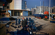 Portrait of a Ford employee on a Fordson tractor agricultural exhibition stand in Paris in 1961. Standing surrounded by agricultural ploughs and tractor farming accessories, the man of unknown nationality is fressed in a smart jacket and tie and may be responsible for progress and construction of this company stand. This is an annual expo of farming equipment such as tractors and this stand belongs to Ford, whose employees are over for this important exhibition in the industry calendar. The picture was recorded on Kodachrome (Kodak) film.