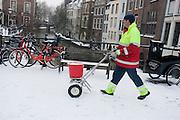 Een medewerker van de gemeente Utrecht loopt met een karretje om de voetpaden te strooien.