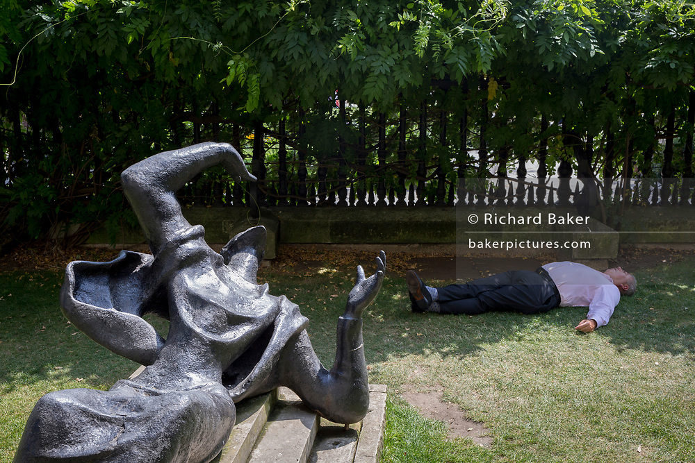 As heatwave temperatures climb to record levels - the hottest day of the year so far - a Londoner sleeps in the shade next to the sculpture entitled Becket by Bainbridge Copnall (1973), in the City of London (the capital's financial district aka the Square Mile) during a hot lunch-hour in St. Paul's Cathedral Churchyard, on 25th July 2019, in London, England.