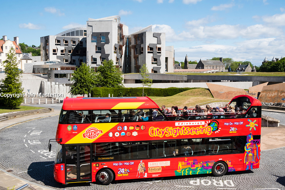 Tourist sightseeing bus outside the Scottish Parliament building at Holyrood in Edinburgh, Scotland, United Kingdom.