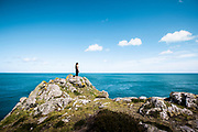 Woman out for a run and stopping to take in the views of the sea from the top of the rocks and cliffs on the north coast of Jersey, Channel Islands