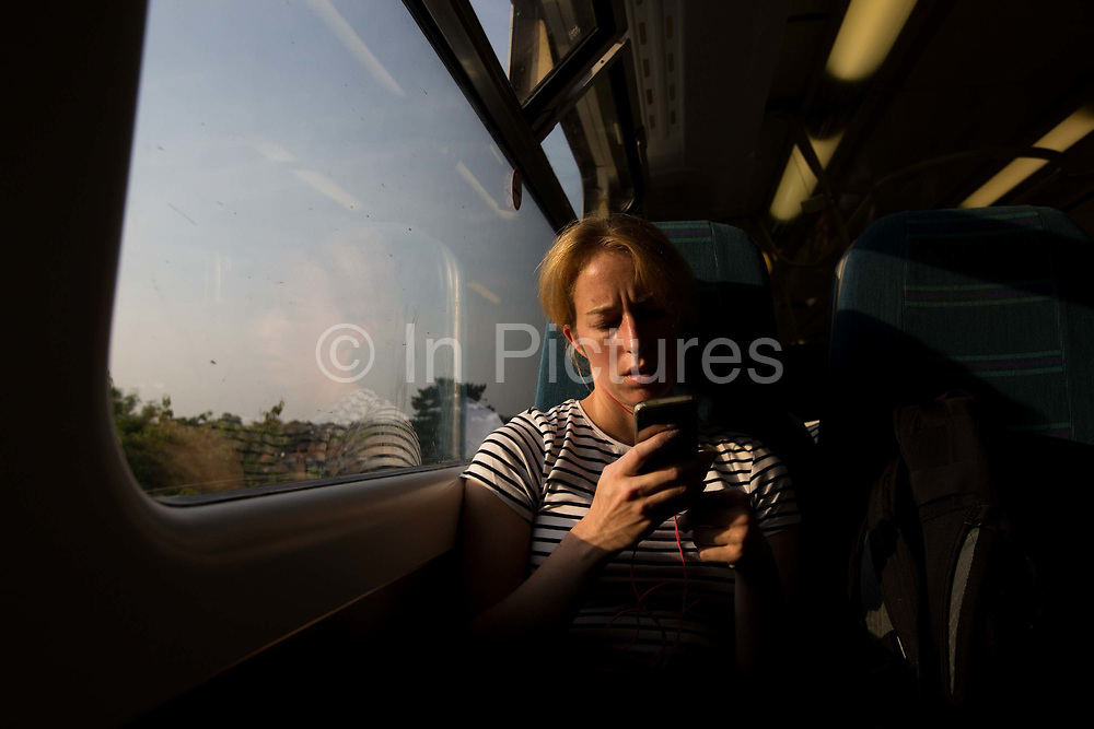 A woman looks at her mobile phone whilst on a train on 19th June 2017 in London, United Kingdom.  From the series Our Small World, an observation of our mobile phone obsession.