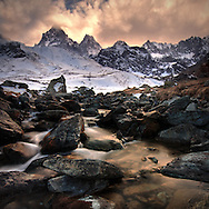 Early spring at Pian del Re, a plateau in the Western Alps famous for featuring the sources of the Po, the longest italian river. The towering pyramid  of the Monviso lies in the background. Taken at sunset at the end of March, This is a stitch of two verticals.