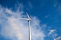 Wind turbine rises into cloudy blue sky