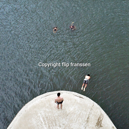 Nederland, Nijmegen, 1-8-2020 Een warme dag in de zomer . Mensen trekken naar de oevers van de waal en de spiegelwaal in het rivierpark aan de overkant van Nijmegen . Vanaf een van de peilers van de spoorbrug duiken jongens in het water . De warmte, hoge temperatuur, drijft mensen naar het water . Het is verboden in de rivier te zwemmen vanwege de stroming en het drukke scheepvaartverkeer . . Vanwege de coronadreiging moet afstand gehouden worden, maar vooral jongeren, jonge mensen, zitten soms in groepen bij elkaar . Foto: ANP/ Hollandse Hoogte/ Flip Franssen