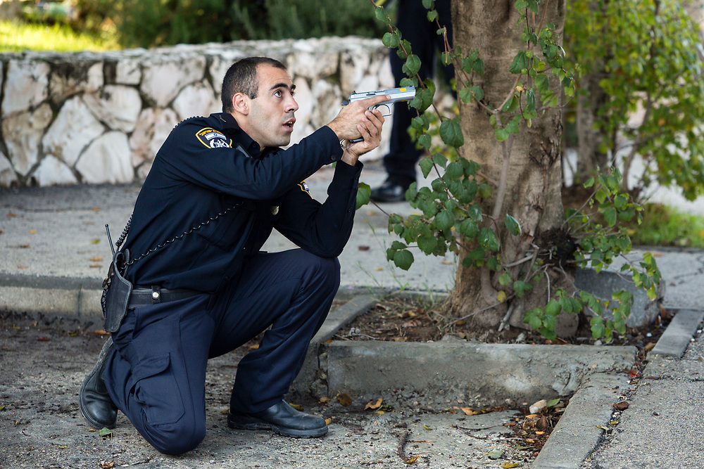 An Israeli policeman takes position near the scene of an attack in a Synagogue in Jerusalem, Israel, on November 18, 2014. Two Palestinian men armed with axes, knives and guns  attacked worshippers praying inside the Synagogue, killing four people being shot dead by police, Israeli officials said.