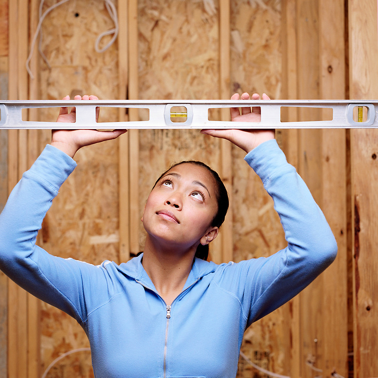 Woman looking up at a carpenters level.