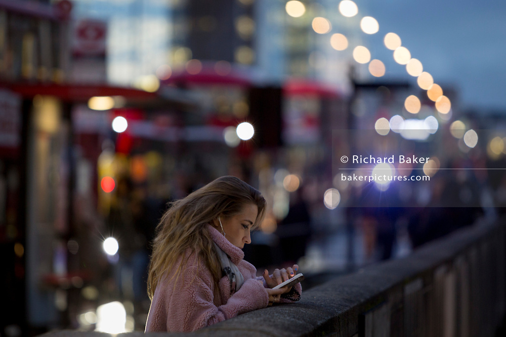 A lady checks messages on London Bridge during the evening rush-hour, on 7th November 2018, in London, England.