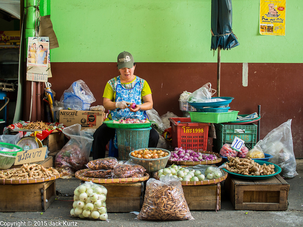 03 APRIL 2015 - CHIANG MAI, CHIANG MAI, THAILAND: A vendor prepares onions for sale in the market in Chiang Mai, Thailand.       PHOTO BY JACK KURTZ