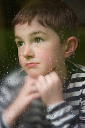 Boy with Hands on Chin behind Rainy Window