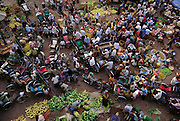 A bird's-eye view of Phnom Penh's Wholesale Market showing how busy traffic moving through the streets can scarcely be differentiated from the buyers and sellers. Vats of deep-frying crickets as well as small frogs and whole small birds are found in this early morning market, Phnom Penh, Cambodia. (Man Eating Bugs page s 44,45)