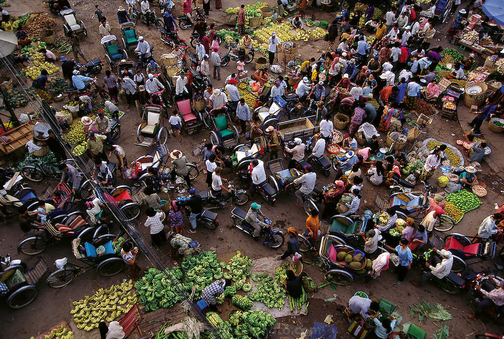A bird's-eye view of Phnom Penh's Wholesale Market showing how busy traffic moving through the streets can scarcely be differentiated from the buyers and sellers. Vats of deep-frying crickets as well as small frogs and whole small birds are found in this early morning market, Phnom Penh, Cambodia. (Man Eating Bugs: The Art and Science of Eating Insects)