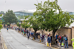 Licensed to London News Pictures. 28/06/2021. London, UK. As Wimbledon Centre Court looms in the distance, long queues form outside the All England Lawn Tennis Club in Wimbledon, southwest London this morning on the first day of the Championships as weather forecasters predict thunderstorms and showers for the next three days. The 2021 AELTC Tennis Championships at Wimbledon, southwest London is back today for the first time in two years after it was cancelled last year due to the Covid-19 pandemic. However, capacity is down by 50% and fans must pre-ordered tickets with no overnight camping or queuing. Photo credit: Alex Lentati/LNP