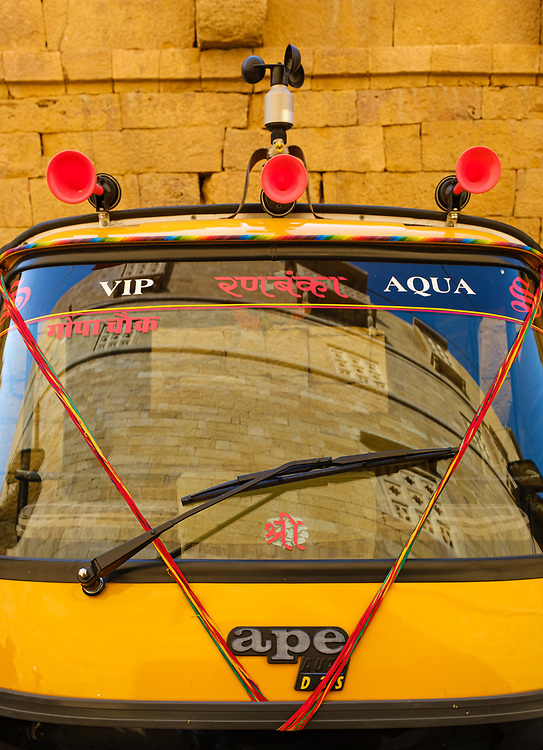 """JAISALMER, INDIA - CIRCA NOVEMBER 2018: View Motor rickshaw windshield and Jaisalmer fort reflection.  Jaisalmer is also called """"The Golden City, and it is located in Rajasthan. . The town stands on a ridge of yellowish sandstone, and is crowned by the ancient Jaisalmer Fort."""