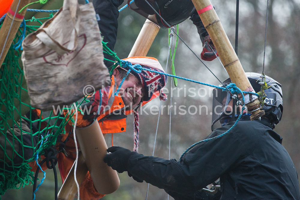 Denham, UK. 8th December, 2020. Dan Hooper, widely known as Swampy in the 1990s, grimaces as bailiffs work to remove him from a bamboo tripod positioned in the river Colne. The climate and roads activist had occupied the tripod the previous day in order to delay the building of a bridge as part of works for the controversial HS2 high-speed rail link and a large security operation involving officers from at least three police forces, the National Eviction Team and HS2 security guards was put in place to facilitate his removal.