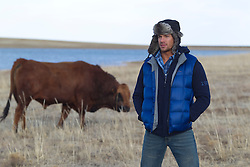 handsome man in winter clothes standing near a bull on a ranch in New Mexico