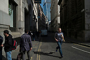 Street scene of a man running, holding a baguette in the City of London, England, United Kingdom.
