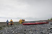 Group carries kayaks across rocky beach on a rainy and overcast day in Seward, Alaska.