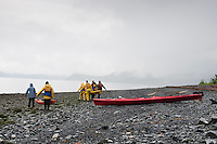 Group carries kayaks across rocky beach on a rainy and overcast day in Seward, Alaska.