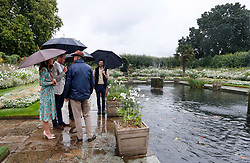 The Duke and Duchess of Cambridge and Prince Harry (partially obscured at centre rear) visit the White Garden in Kensington Palace, London, as they meet with representatives from charities supported by Diana, the Princess of Wales.