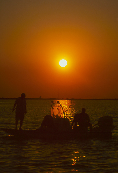 Stock photo of two men fishing from their boat at sunset