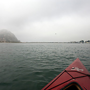 The well known smoke stacks from the Morro Bay Power Plant rise above Morro Bay as Morro Rock is shrouded in fog.