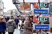 Nederland, Netherlands, Nijmegen, 4-4-2015 Markt in het centrum van Nijmegen. Bij een kraam hangen vlaggen vant NEC. Gisteren werden ze kampioen in de jupiler league en vandaag is de huldiging. De bus met spelers is juist lagsgekomen en rijdt in de verte weg..FOTO: FLIP FRANSSEN/ HOLLANDSE HOOGTE