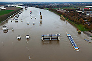 Nederland, Limburg, Gemeente Venlo, 15-11-2010. Het sluis en stuwcomplex Belfeld bij hoogwater van de Maas. De stuw is gestreken en de scheepvaart maakt gebruik van de vaargeul naast de stuwtorens. De schutsluizen staan geheel onder water, de bedieningsgebouwen staan op kolommen boven het water. Het complex is gebouwd in het kader van de kanalisatie van de Maas in de jaren 1918 - 1929. .Lock and weir complex Belfeld at high waters of river Meuse. The weir is 'lifted' allowing for ships to passe. The normal shipping locks lock are completed flooded (and under water). The control buildings are build on columns. The whole complex was built in the context of the canalization of the Meuse in the years 1918 to 1929..luchtfoto (toeslag), aerial photo (additional fee required).foto/photo Siebe Swart