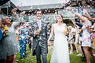 Bride and groom walking through confetti tunnel