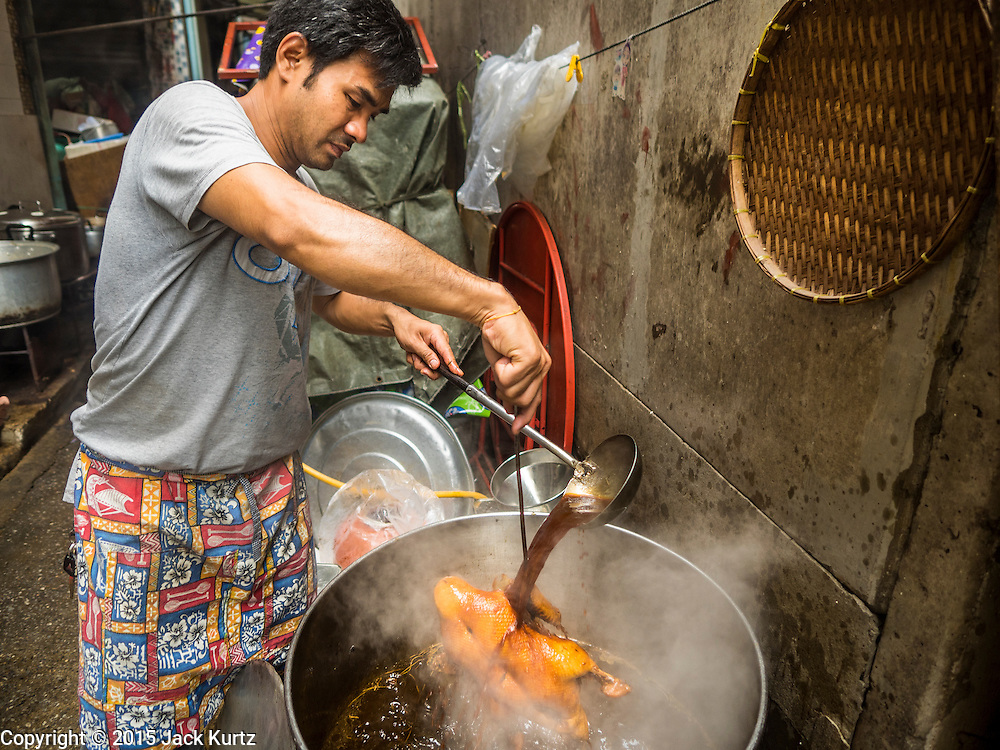 28 AUGUST 2015 - BANGKOK, THAILAND: A man cooks stewed duck for Hungry Ghost Day offerings in Bangkok's Chinatown. Mahayana  Buddhists believe that the gates of hell are opened on the full moon of the seventh lunar month of the Chinese calendar, and the spirits of hungry ghosts allowed to roam the earth. These ghosts need food and merit to find their way back to their own. People help by offering food, paper money, candles and flowers, making merit of their own in the process. Hungry Ghost Day is observed in communities with a large ethnic Chinese population, like Bangkok's Chinatown.       PHOTO BY JACK KURTZ