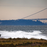 A fisherman working the shoreline at Sandy Hook NJ during a powerful coastal storm (nor'easter) pummeled the coastline.   The fall fishing run of striped bass and bluefish is legendary at the park.  Behind the fisherman is the Verranzano-Narrows Bridge linking Staten Island and Brooklyn together.