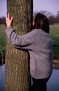 A912RF Woman hugging a tree