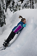 Young girl falling into snowbank head first while playing in forest in winter, Calaveras Big Trees State Park, Calaveras County, California
