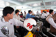 Scooters and other passengers on foot disembark from one of Shanghai's regular ferries which cross from Pudong to Xinmatou in Puxi in Shanghai, China. Here on the Puxi side the switch over of passengers is a frenetic scramble in keeping with the general way on Shanghai's streets, which can feel like a fight to be first, big pushing in front of small to take top place.
