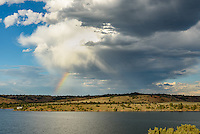 A rainbow appears in front of a small rain shower over Montana's Tongue River Reservoir.