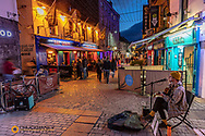 Street musician performs along vibrant Quay Street at dusk in downtown Galway, Ireland
