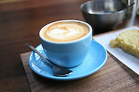 Close up of a cup of cappuccino coffee in a blue cup and saucer with cake